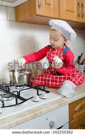 Little cook adds spice to the pot of soup - stock photo