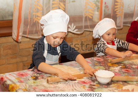 Little cook. Children make pizza. Master class for children on cooking Italian pizza. Young children learn to cook a pizza. Kids preparing homemade pizza - stock photo