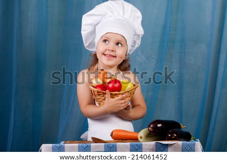 Little cook prepares healthy food, cheery kitchen boy at the table, happy kitchen boy holding a basket of vegetables - stock photo