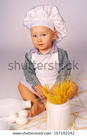 Little cook with bread, milk, eggs and spaghetti