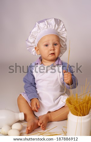 Little cook with milk, eggs and spaghetti