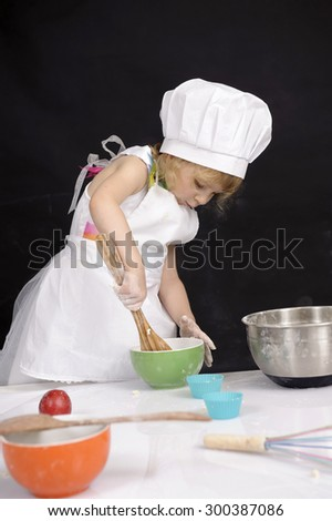 Little cooking girl with chef hat and apron - stock photo