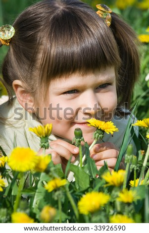Little cool smiling girl is smelling at the dandelion on the flowering meadow - stock photo