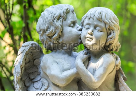 Little couple angel sculpture in green garden - stock photo