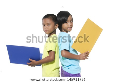 little couple reading book standing on white background standing back to back on white background - stock photo