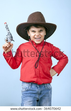 Little cowboy is threating and making a dangerous face to his enemies. - stock photo