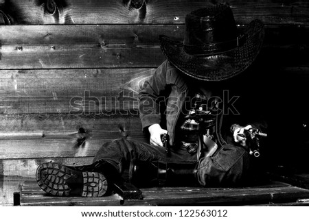 little cowboy sitting on wooden box near wall and holding pistols - stock photo
