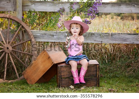 Little Cowgirl.  Adorable little girl pretending to be a cowgirl.   - stock photo