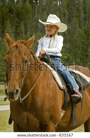 Little Cowgirl on Her Horse - Focus on Girl - stock photo
