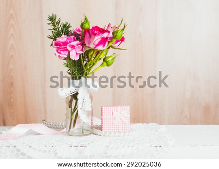 Little cozy bouquet in glass bottle over crochet doily. Vintage styled - stock photo