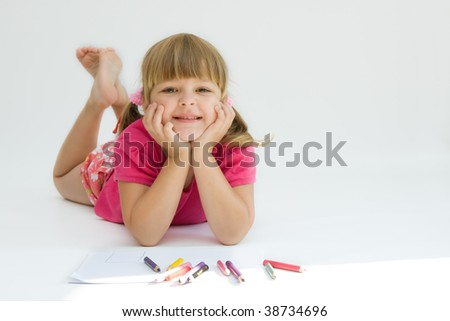 little, creative girl drawing with crayons on white