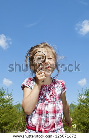 little curious girl with the magnifying glass - stock photo
