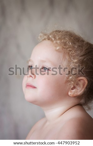 little curly blond Caucasian girl looking dreamily into the distance light smile - stock photo
