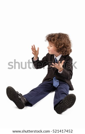 Little curly boy in a business suit sitting on the floor, screaming and gesturing with his hands. White background.