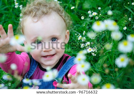 Little curly girl on the meadow - stock photo