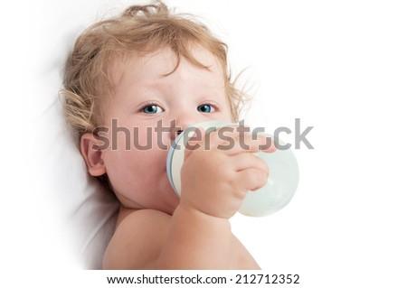 little curly-headed baby sucks a bottle of milk - stock photo