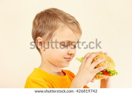 Little cut boy with a tasty hamburger - stock photo