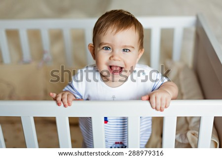 Little cute adorable little blond boy in a striped bodykit is in the nursery with white crib and laughs - stock photo