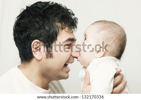 Little cute baby biting nose of his father - stock photo