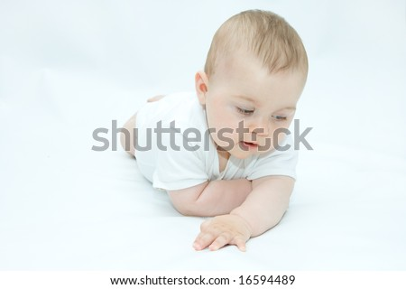 little, cute baby boy lying on white background