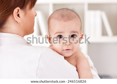 Little cute baby child with doctor pediatrician - stock photo