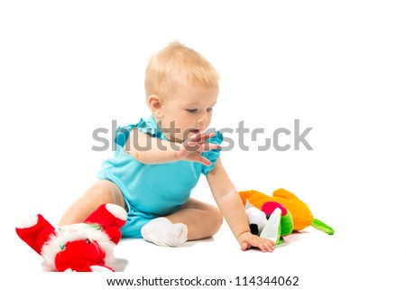 Little cute baby-girl in blue dress playing with toys