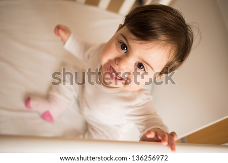 Little cute baby smiling at camera in her cot - stock photo