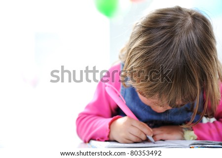 Little cute blond baby girl is drawing with pencil on paper, large copy space beside - stock photo