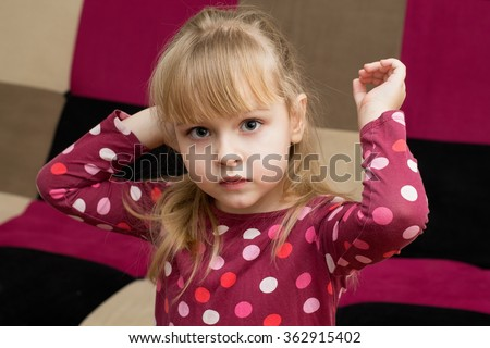 Little cute blond girl in a  bright dress , hands up  - stock photo