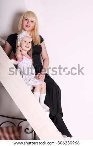 Little cute blond girl in dress sitting on wooden stairs with her mother - stock photo