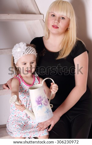 Little cute blond girl in dress sitting on wooden stairs with her mother and keeps watering. Focus on girl - stock photo