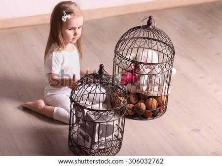 Little cute blond girl playing in room with cages filling toys. Focus on cage - stock photo