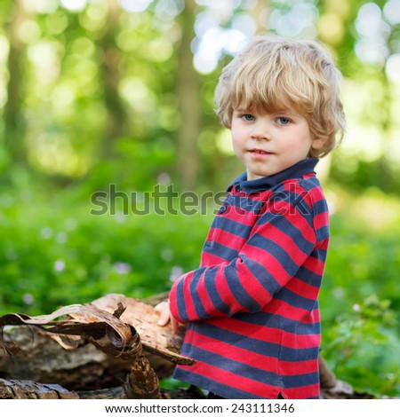 Little cute blond kid boy having fun in summer forest. Active leisure for children outdoors, on warm summer day. Toddler learning nature. - stock photo