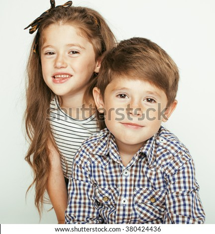 little cute boy and girl hugging playing on white background, happy family smiling - stock photo