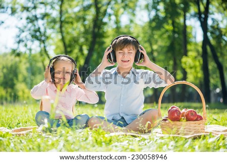 Little cute boy and girl in summer park - stock photo