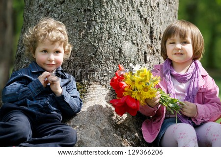 little cute boy and girl on date in park - stock photo