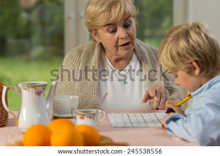 Little cute boy and his granny doing homework - stock photo