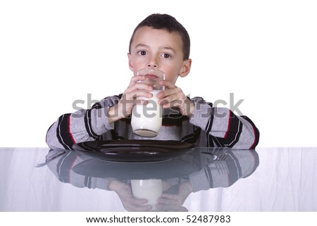 Little Cute Boy Drinking Milk at the Table