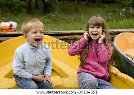 little cute boy five years old shouting sitting on boat.  little cute girl seven years old close her ears by hands. Noisy day - stock photo