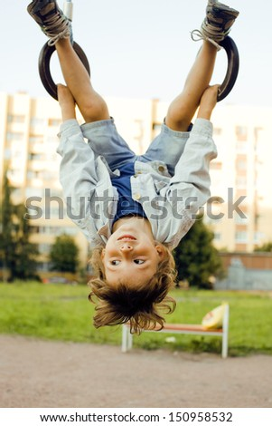 little cute boy hanging on gymnastic ring - stock photo