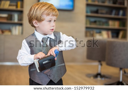 Little cute boy in business clothes with a puncher and stapler in the business center