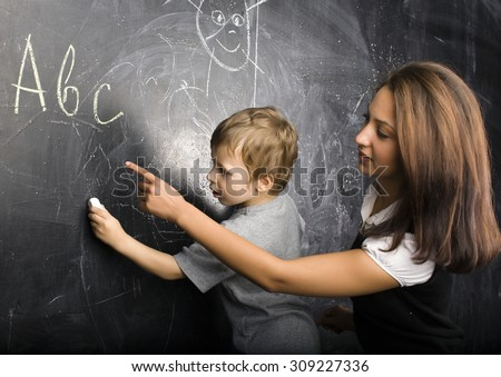 little cute boy in glasses with young real teacher, classroom studying at blackboard school kido - stock photo