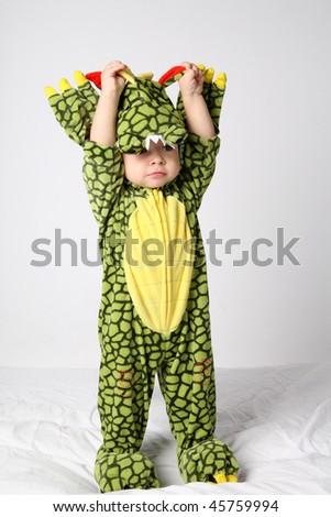 Little cute boy in green dinosaur costume. - stock photo