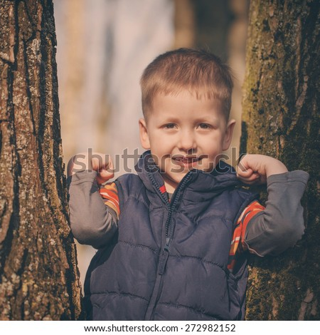 Little cute  boy in stands among the trees in sunny spring day. Toned image - stock photo