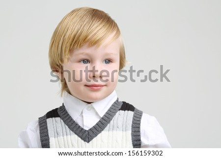 Little cute boy in vest and shirt looks away on grey background.
