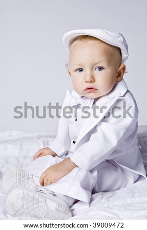 Little cute boy in white suit. - stock photo