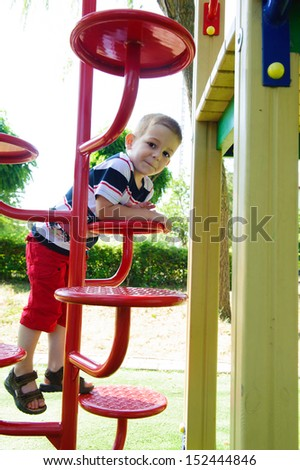 Little cute boy is climbing at playground