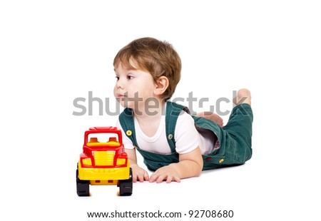 Little cute boy laying down behind a plastic toy truck. - stock photo