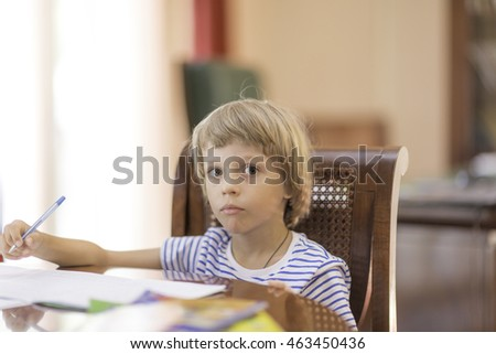 little cute boy makes homework getting ready for school