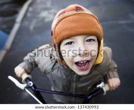 little cute boy on bicycle smiling close up